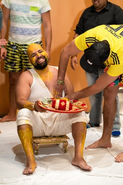 Indian groom being smeared with the turmeric paste.