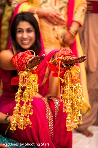 Indian bride with her bracelets with hanging bells .