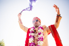Indian groom pouring purple smoke for his baraat procession.