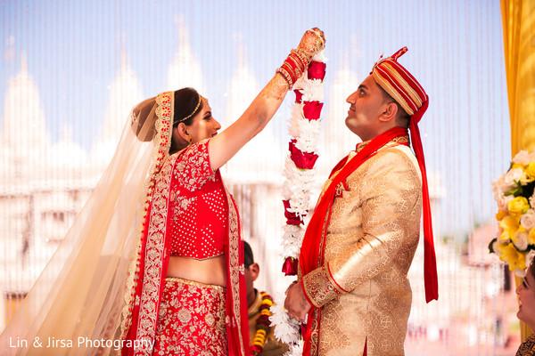 Maharani putting garland to rajah at wedding ceremony.