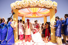Joyful Indian bride and groom walking around sacred fire.