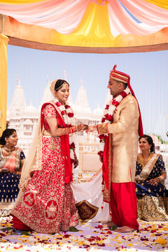Indian bride putting ring to groom.