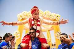 Indian groom lifted by a groomsmen at baraat procession.