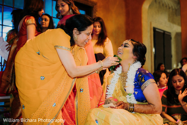 Maharani getting turmeric paste on her face.
