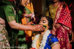 Indian bride  getting Turmeric paste on.