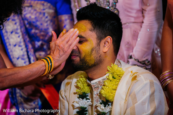 Indian groom getting Turmeric paste on.