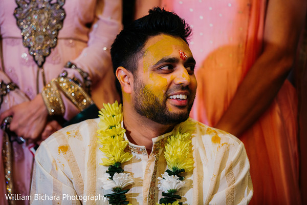 Indian groom getting the turmeric paste on his face.