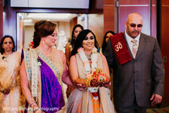 Indian bride walking in to her roka ritual celebration.