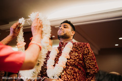 Indian groom getting garlands at his baraat ritual.
