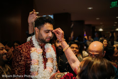 Indian groom holding coconut and getting the red dot on forehead.