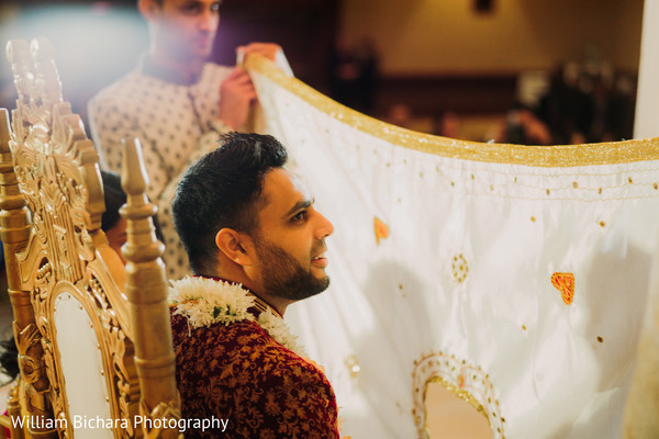 Indian groom being covered with antarpat veil.