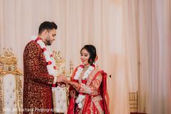 Indian groom putting wedding band to bride.