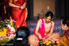 Indian bride putting petals on offerings plate.