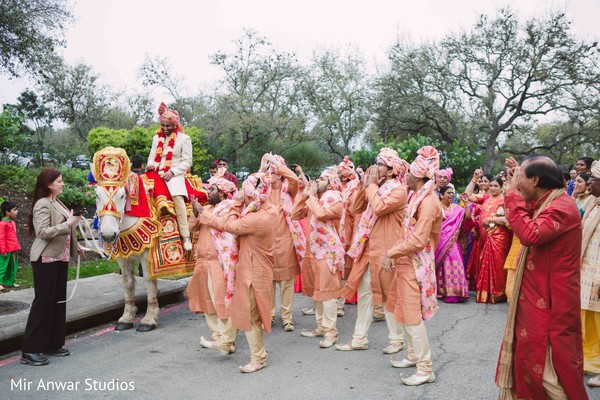Indian groom with groomsmen at baraat celebration.
