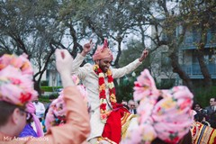 Indian groom on his baraat white horse celebrating.