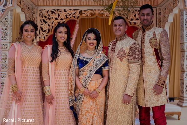 Joyful Indian bride with bridesmaids and groomsmen capture.