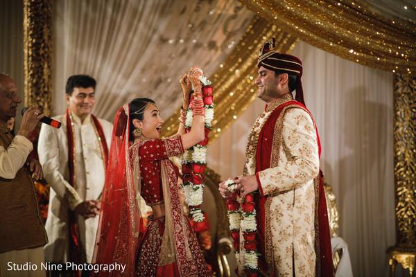 Indian bide putting garland to groom.