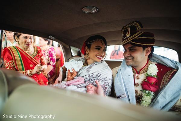 Joyful Indian couple leaving their wedding.