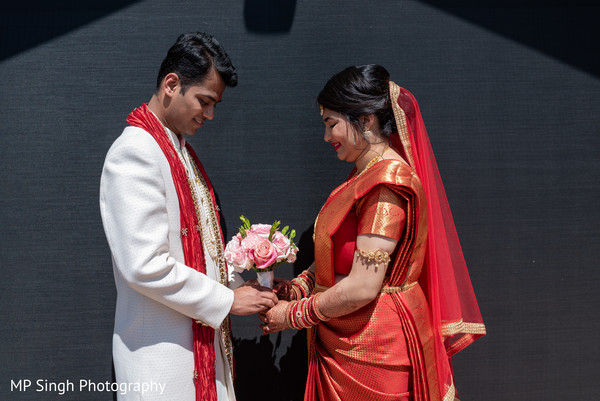 Indian bride and groom holding the bouquet