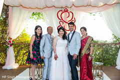 Indian newlyweds posing with family