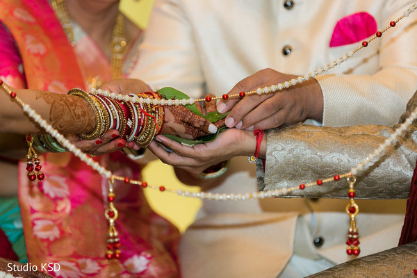 Indian ritual holding areca nut , flower petal and rice on leaf.