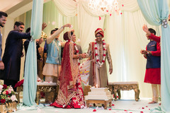 Indian couple being trowed rose petals.
