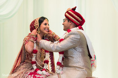 Indian groom putting Indian bride the necklace at ceremony.