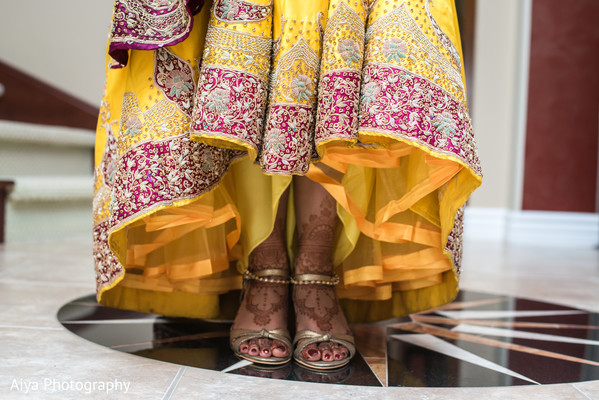 Indian bride putting her ceremony golden shoes.