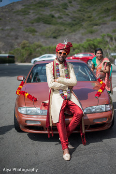Charming Indian groom posing on his baraat vehicle.