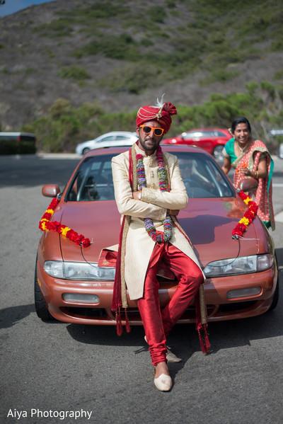 Charming Indian groom posing on his baraat vehicle.