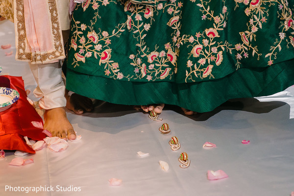 Indian wedding ritual where couple are rolling betel nut with toes.