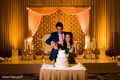 Lovely  Indian bride and groom cutting cake together.