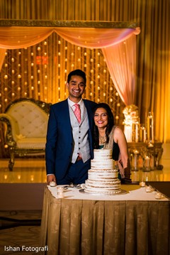 Lovely indian couple cutting the cake.