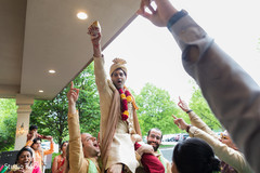 Indian groom being lifted at his baraat celebration.