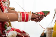 Maharani holding flower petals and rice on leaf.