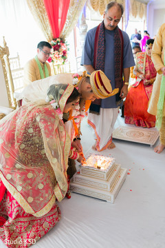 Indian couple pouring rice in to sacred fire.