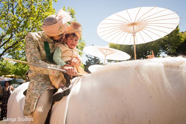 Indian groom with kid during baraat