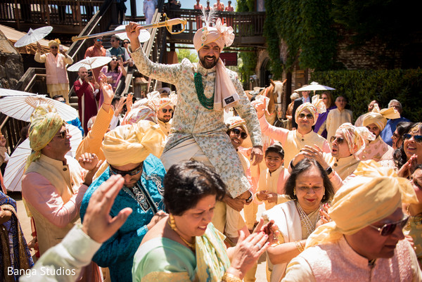 Indian groom lifted by groomsmen at baraat procession.