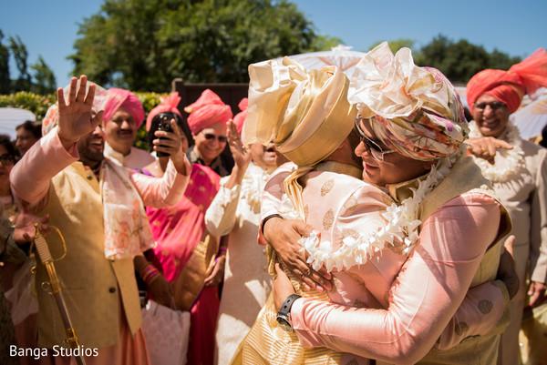 Indian groom with groomsmen hug.