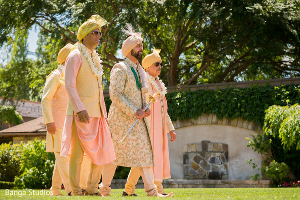 Indian groom walking with groomsmen to ceremony.