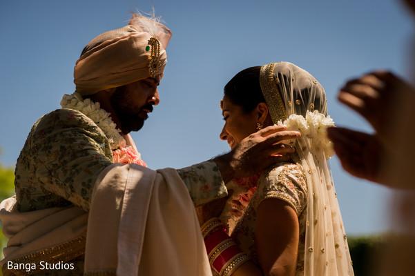 Indian groom putting garland to bride.