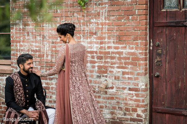 Indian bride and groom on their Smoky Pink reception outfits.