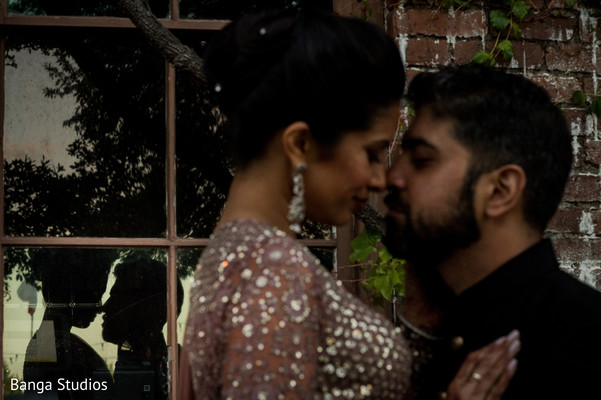 Indian couple's reflection on window glass capture.