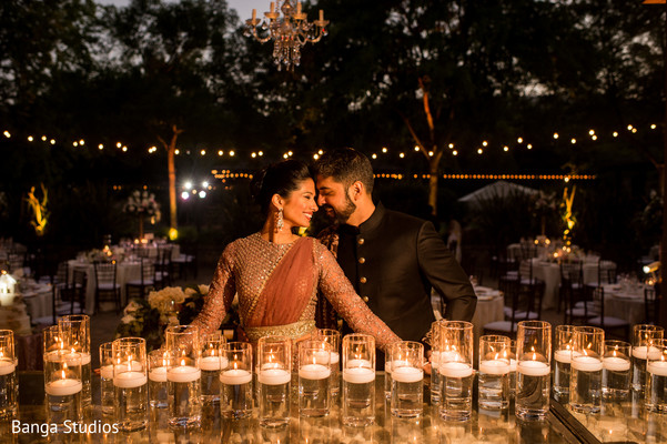 Indian bride and groom posing in front of candles.