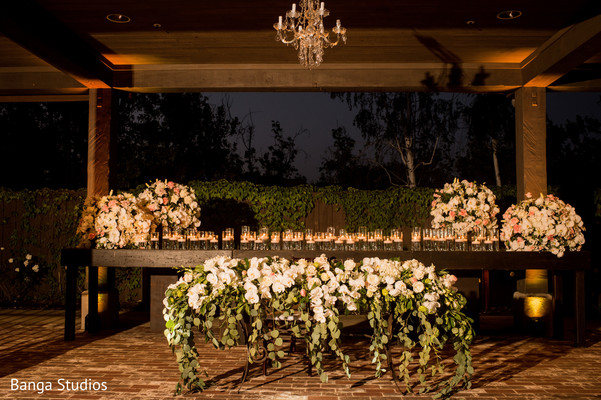 Indian wedding wood table with candles and flowers decorations.
