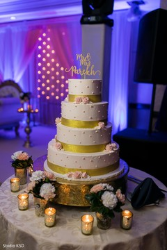 Elegant Indian wedding golden cake decor.