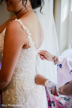 Indian bride putting her white dress.