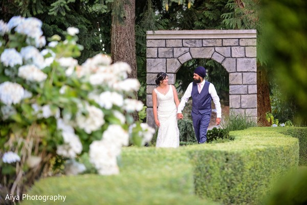 Indian groom and bride walking down the garden