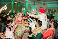 Indian couple being lifted by guests