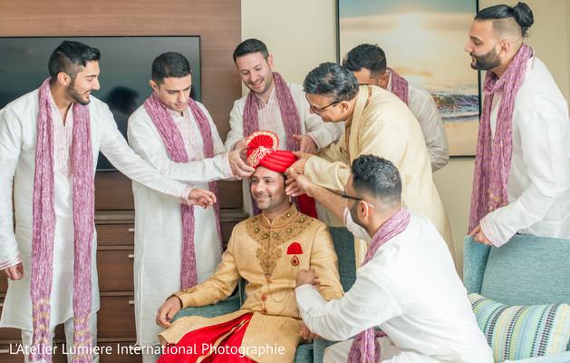 Indian groom being assisted by groomsmen